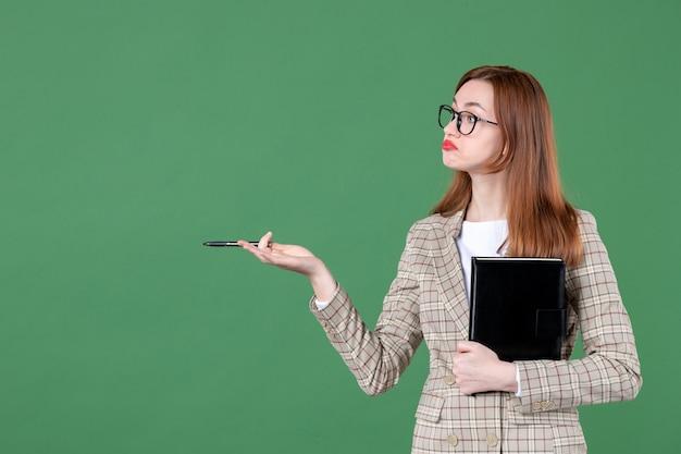 Ritratto di insegnante femminile che tiene il blocco note su green