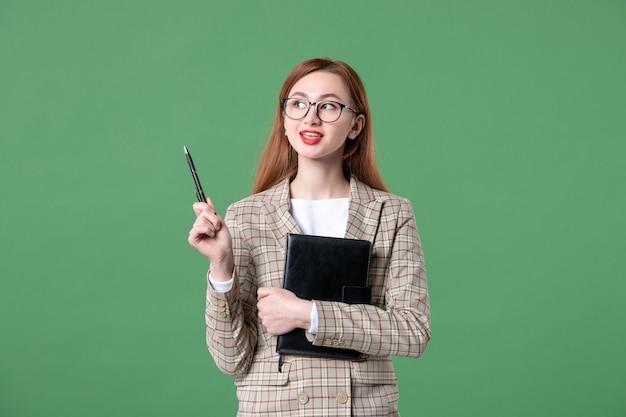 Portrait of female teacher in suit on green