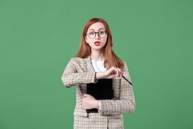 Portrait of female teacher in suit with notepad on green