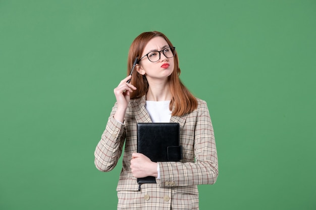 Portrait of female teacher in suit with notepad and pen on green