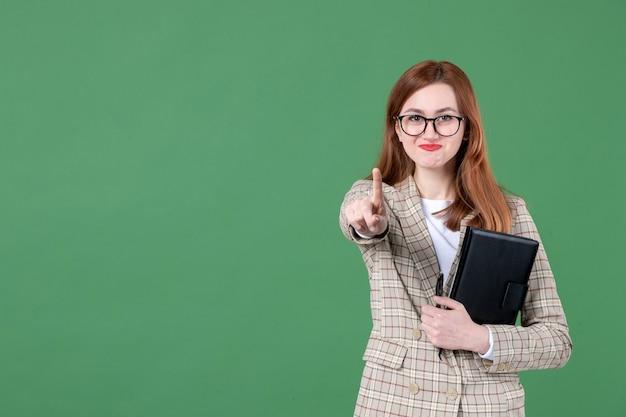 Ritratto di insegnante femminile con blocco note su green