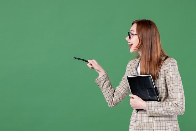 Ritratto di insegnante femminile con blocco note che parla con qualcuno sul verde