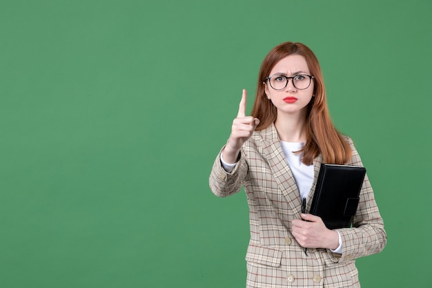 Ritratto di insegnante femminile con blocco note che minaccia sul verde