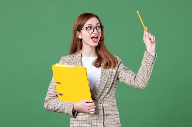 Ritratto di insegnante femminile con file gialli su verde