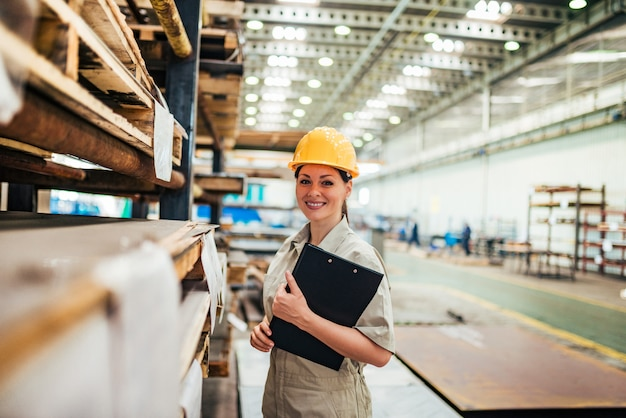 Portrait of a female technician at factory hall.