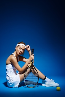 Portrait of a female tennis player with racket and ball sitting on floor