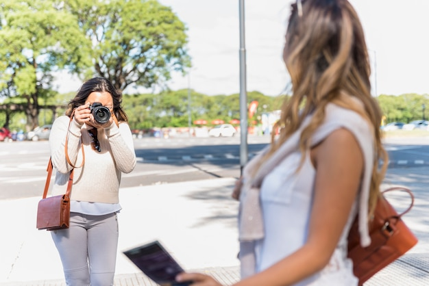 Portrait of a female tourist taking photograph of her female friend from camera