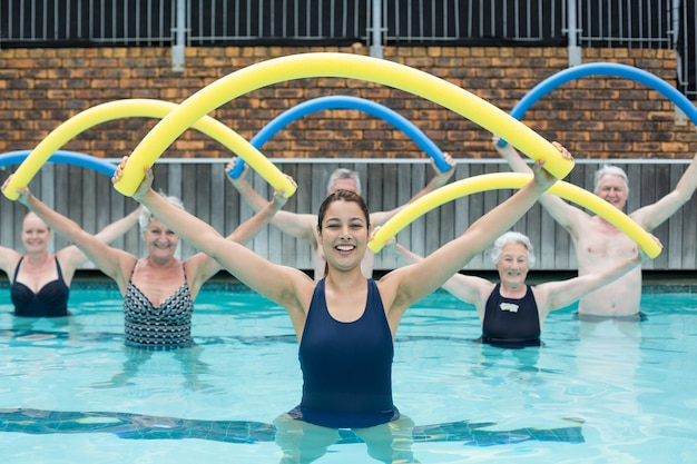 Portrait of female trainer and senior swimmers exercising with pool noodle