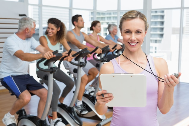 Portrait of a female trainer with people working out at spinning class in gym