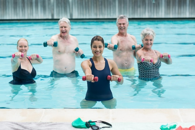 Portrait of female trainer with senior swimmers exercising in swimming pool