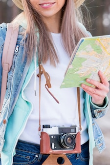 Portrait of a female traveler holding vintage camera and map