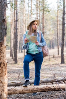 Portrait of a female traveler standing in the forest with map