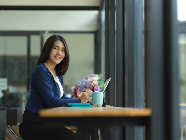 Portrait of female university student smiling to camera while doing assignment in cafe