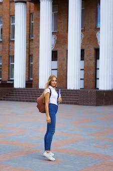 Portrait of female university student standing outside building