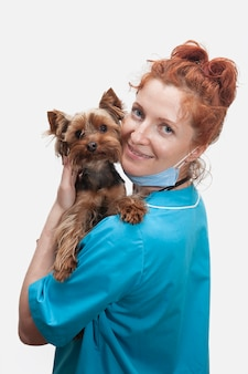 Portrait of female veterinary doctor in medical uniform with dog in hands on isolated white background