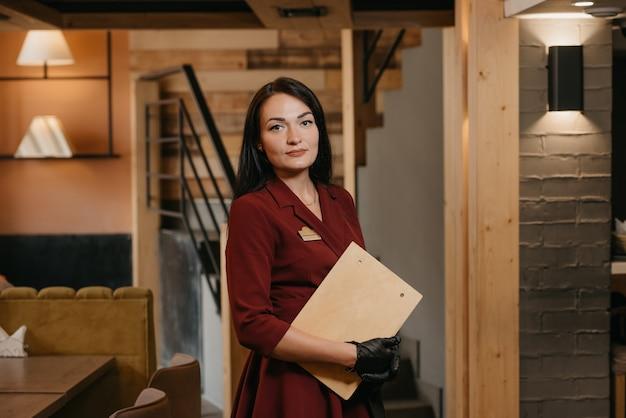 クリップボードを保持している肖像画の女性ウェイトレス