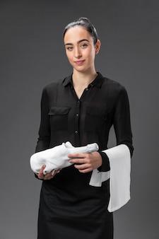 Portrait female waitress with bottle of wine