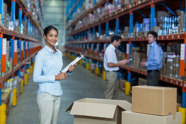 Portrait of female warehouse worker standing with clipboard