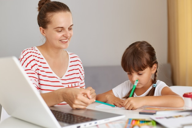 Portrait of female wearing striped casual clothing doing homework with her charming kid, schoolgirl writing home task in exercises, people posing in light room at home, online distance lessons.