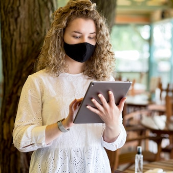 Ritratto femminile con maschera utilizzando tablet