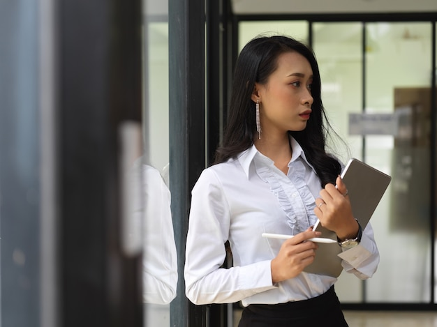 Portrait of female worker holding digital tablet while standing in front of the door to meeting room
