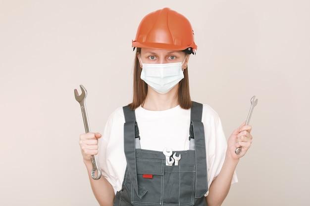 肖像画の女性労働者は、保護マスクの顔、安全ヘルメットとスーツを着用し、大きなネジキーを使用して、手にレンチをかけます。