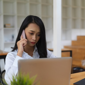 Portrait of female worker talking on the phone while woking with laptop in office room
