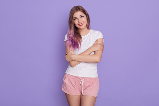Portrait of female of young age wearing casual clothing standing and hugging herself, looking at camera with smile and love, isolated over lilac background.