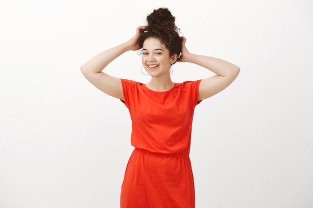 Portrait of femenine confident cute woman in stylish dress, touching combed hair and smiling with tender shy expression