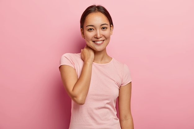 Portrait of feminine girl with pleasant smile, gentle look, touches neck, has delighted face expression, has pleasant talk with close friend, dressed in casual outfit, isolated on pink wall