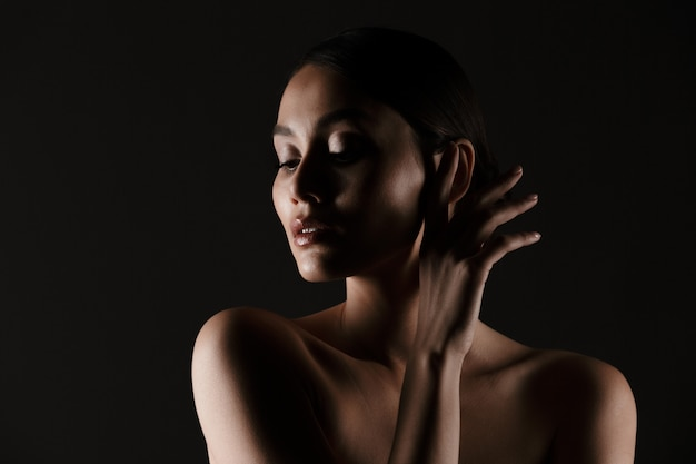 Portrait of feminine tender woman with sensual look looking aside in low lights, isolated over black
