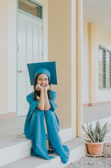 Ritratto di una donna filippina che indossa il suo cappello di laurea, abito e fascia.
