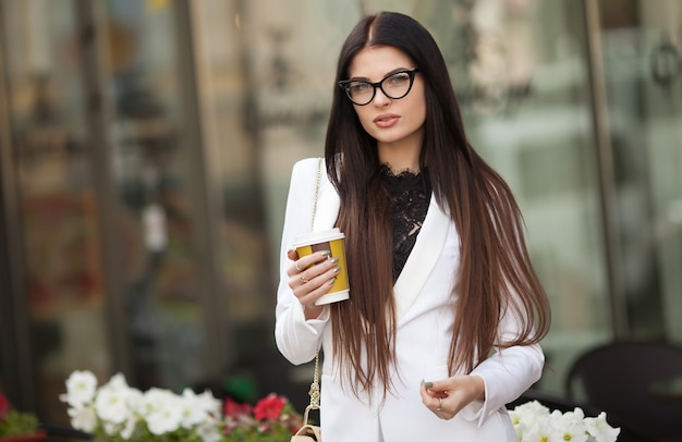 Portrait of financial professional businesswoman holding in hand a cup of coffee while walking to the financial convention to business center.