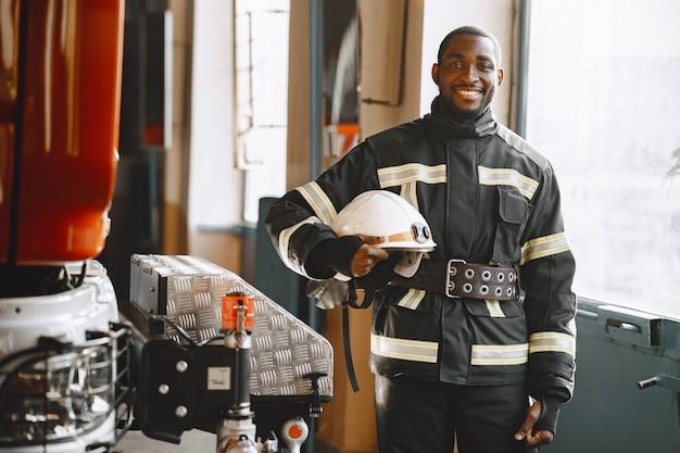 Ritratto di un vigile del fuoco in piedi davanti a un'autopompa antincendio