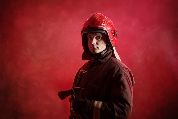 Portrait of firefighter in uniform on dark red
