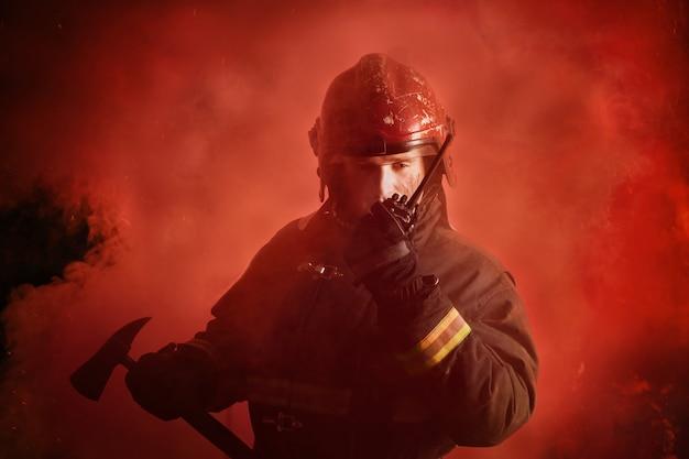 Portrait of firefighter in uniform on dark red