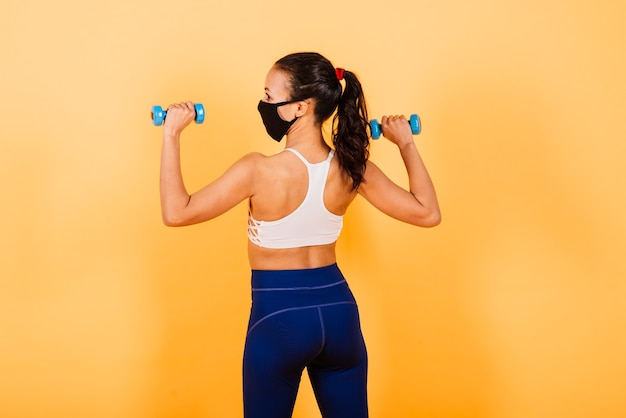 Portrait of fit african woman wearing face mask. sporty woman in fitness wear standing on a yellow background.