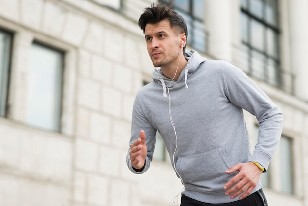 Portrait of fit athlete running outdoors