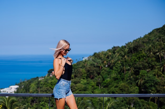 Portrait of fit european woman in swimsuit and denim shorts on vacation