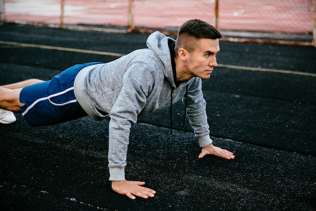 Portrait of a fit handsome sportsman doing plank exercise, practicing pushs up on track road