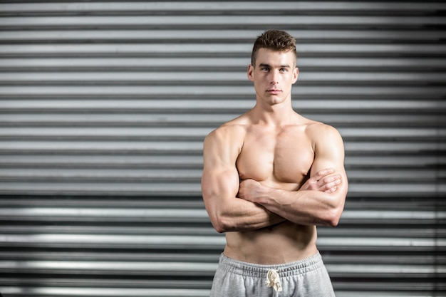 Portrait of fit man with crossed arms at crossfit gym