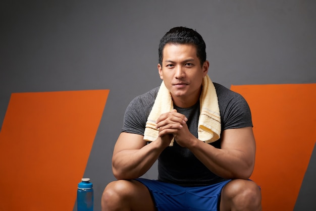 Portrait of fit man with fingers intertwined sitting on gym couch after training