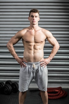Portrait of fit man with hands on hips at crossfit gym
