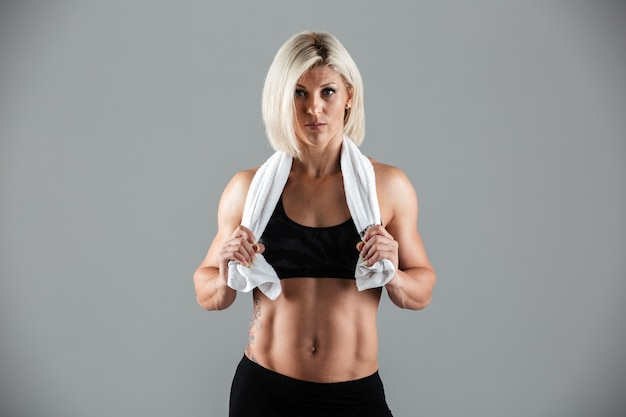 Portrait of a fit muscular adult woman holding a towel