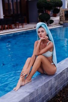 Ritratto di giovane donna caucasica in forma sottile in bikini blu fuori dalla villa in piscina al giorno di pioggia