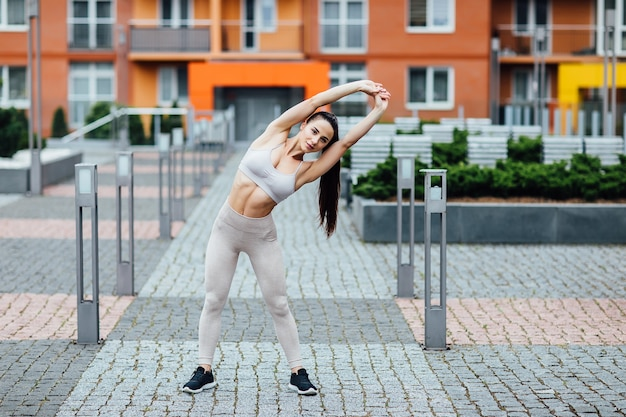 Portrait of fit and sporty young woman doing stretching in city.