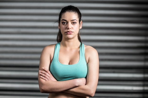 Portrait of fit woman with crossed arms at gym