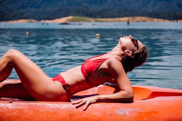 Portrait of fit young caucasian tourist woman in bikini relaxing on kayak at beautiful lake in thailand. female on vacation enjoying sunny day.