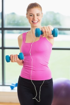Portrait Of A Fit Young Woman Exercising With Dumbbells In