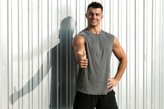 Portrait of fitness athlete man with thumb up gesture. nice musculature man.
